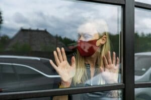 depresive woman in face mask looking out the window, staying home in quarantine, covid-19 lockdown